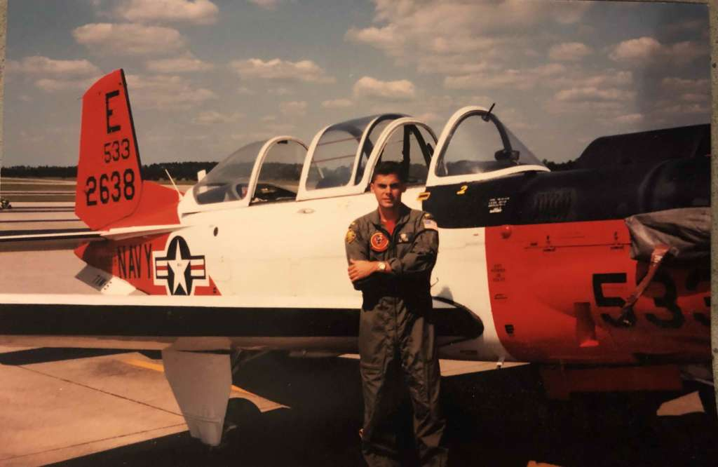 Mike Garcia in uniform posing in front of a red and white jet.