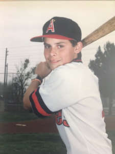 Mike Garcia as a child wearing a baseball uniform and posing with a bat.
