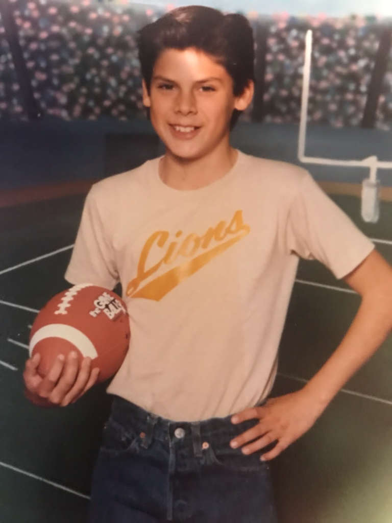 Mike Garcia as a child holding a football.