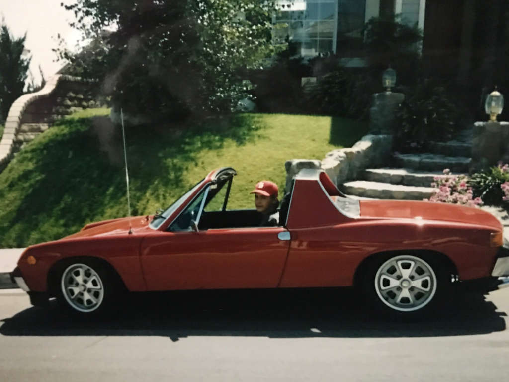 Young Mike Garcia sitting in a red convertible in front of a suburban home.