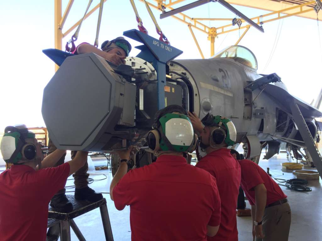 Five men with protective headsets work on a jet engine.