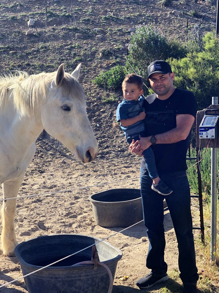 Mike Garcia holding son Jett (age 2) standing next to a white horse.